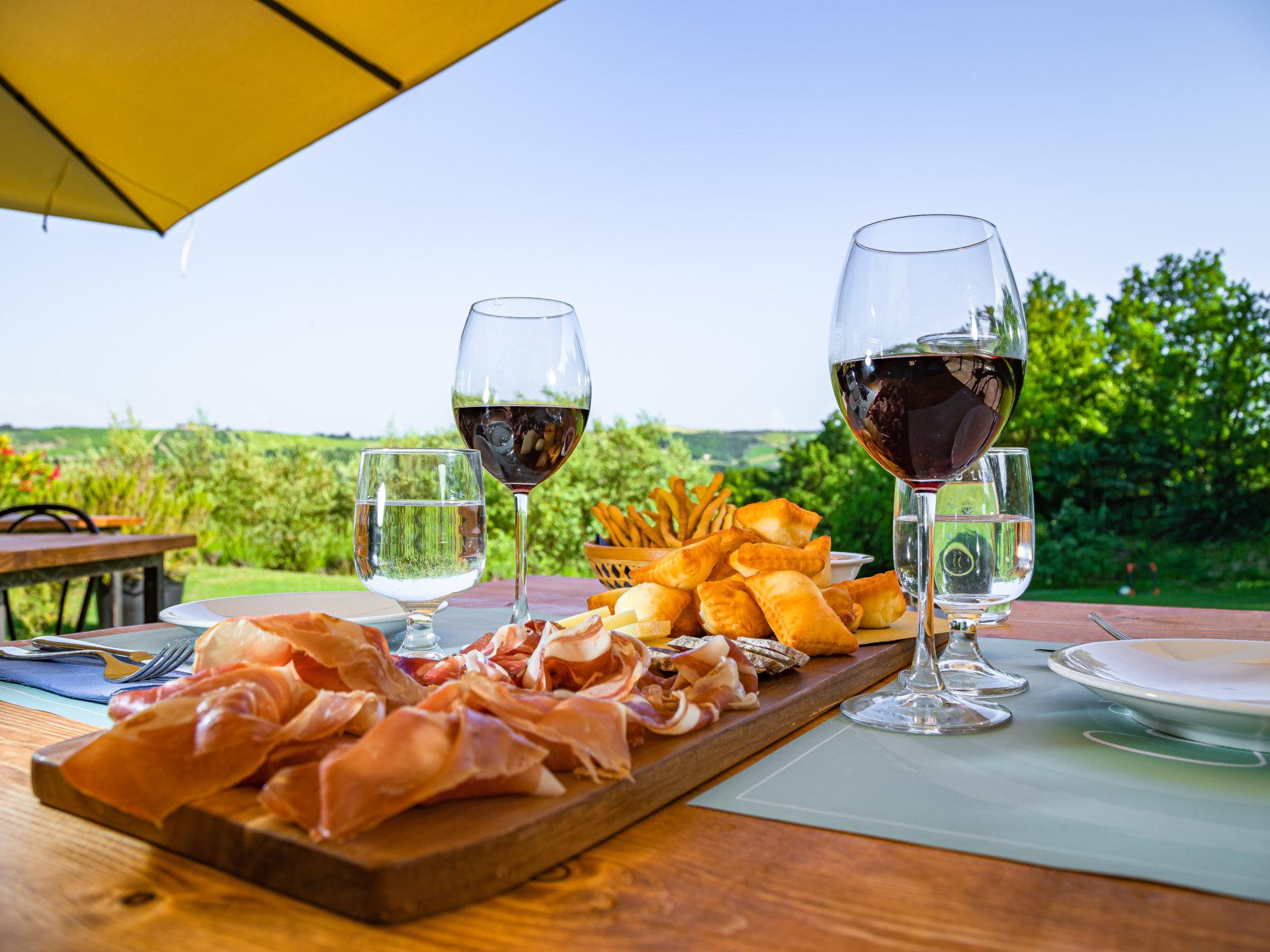 Un piatto di salumi con gnocco fritto e un bicchiere di vino